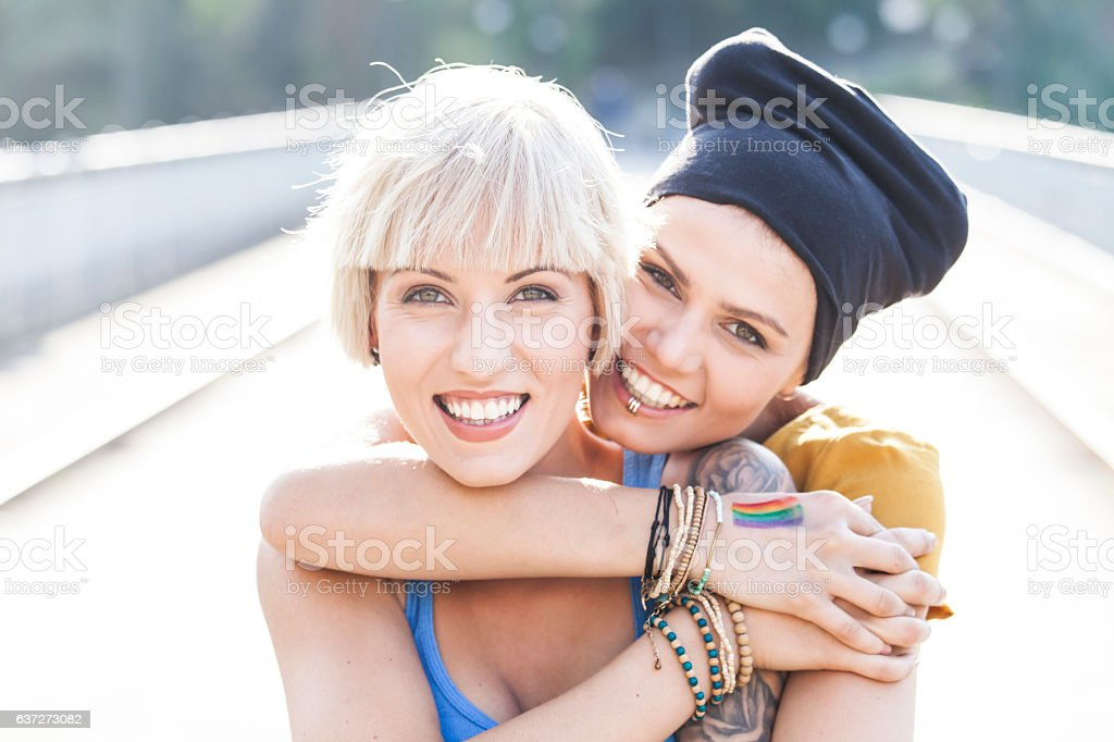 Two women embracing on bridge and looking at camera stock photo