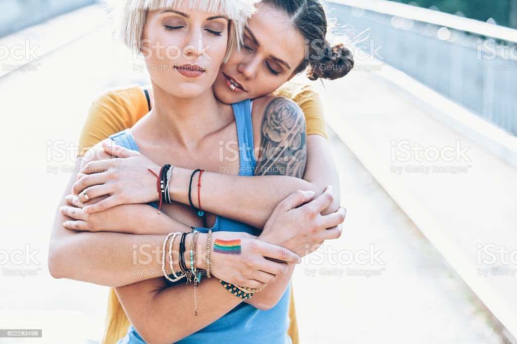 Two women embracing on bridge with eyes closed stock photo