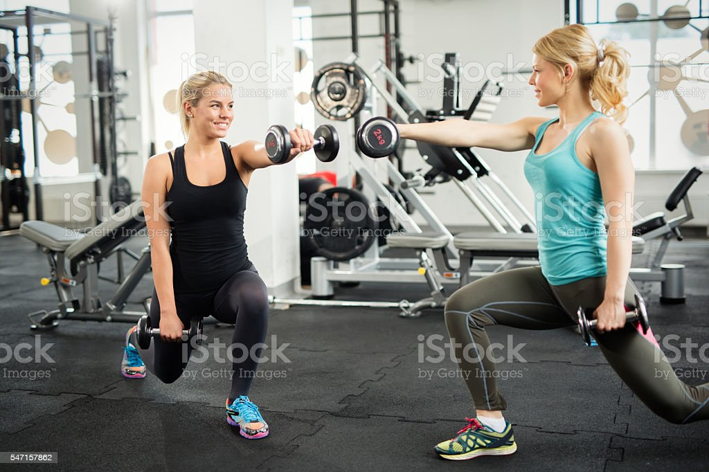 Two women exercising lunges with dummbells at the gym. stock photo