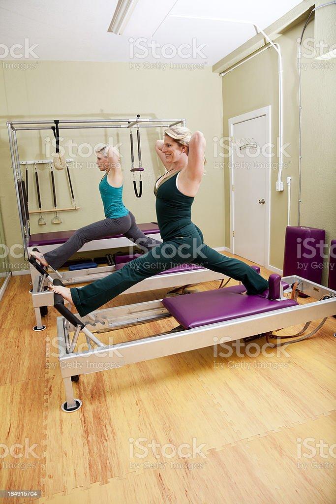 Two women exercising on pilates reformer machines stock photo