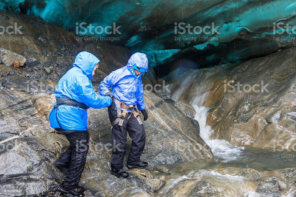 Two women explore glacier terminus stock photo