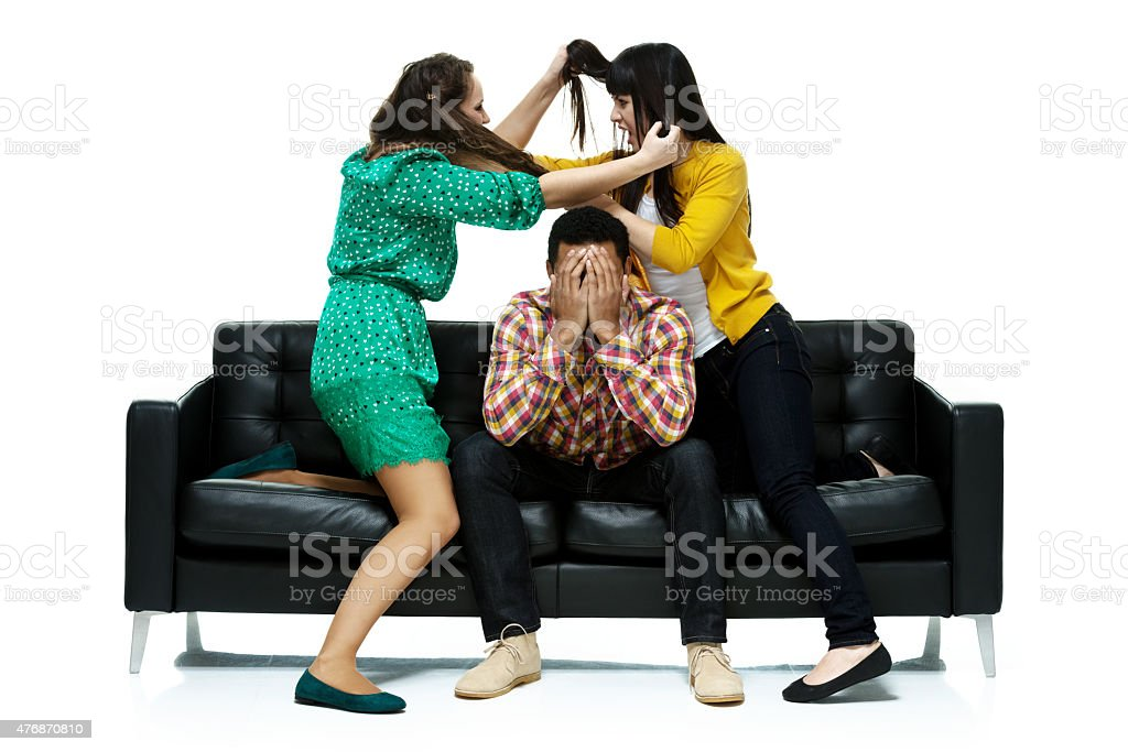 Two women fighting over a man stock photo