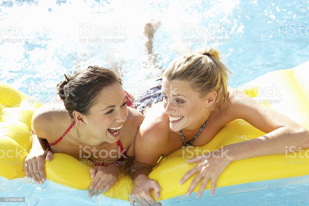 Two women friends having fun in pool royalty-free stock photo