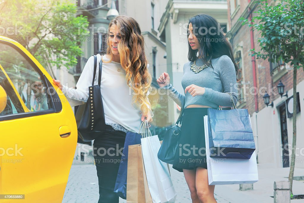 Two women get on a taxi stock photo