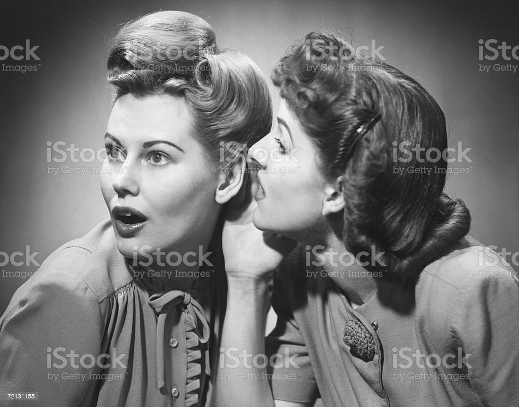 Two women gossiping in studio (B&W) stock photo