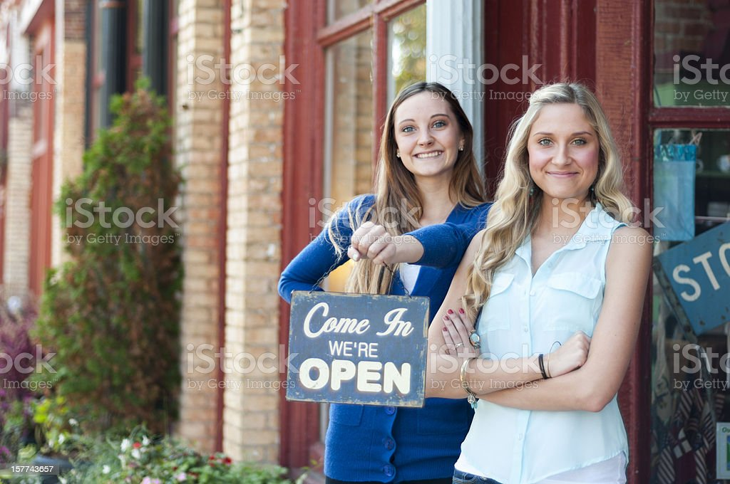 Two women greeting in front of their shop holding open sign royalty-free stock photo