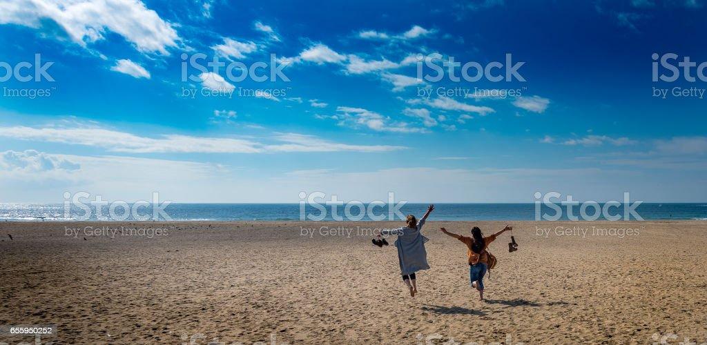 Two women happy running stock photo