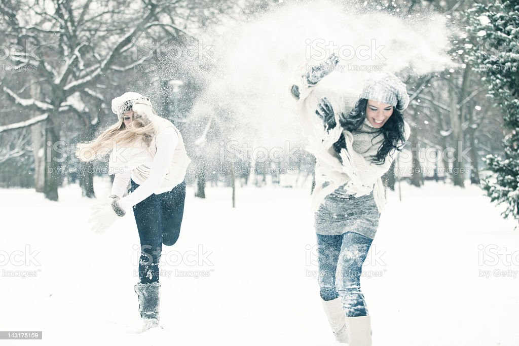 Two women having a snow ball fight stock photo