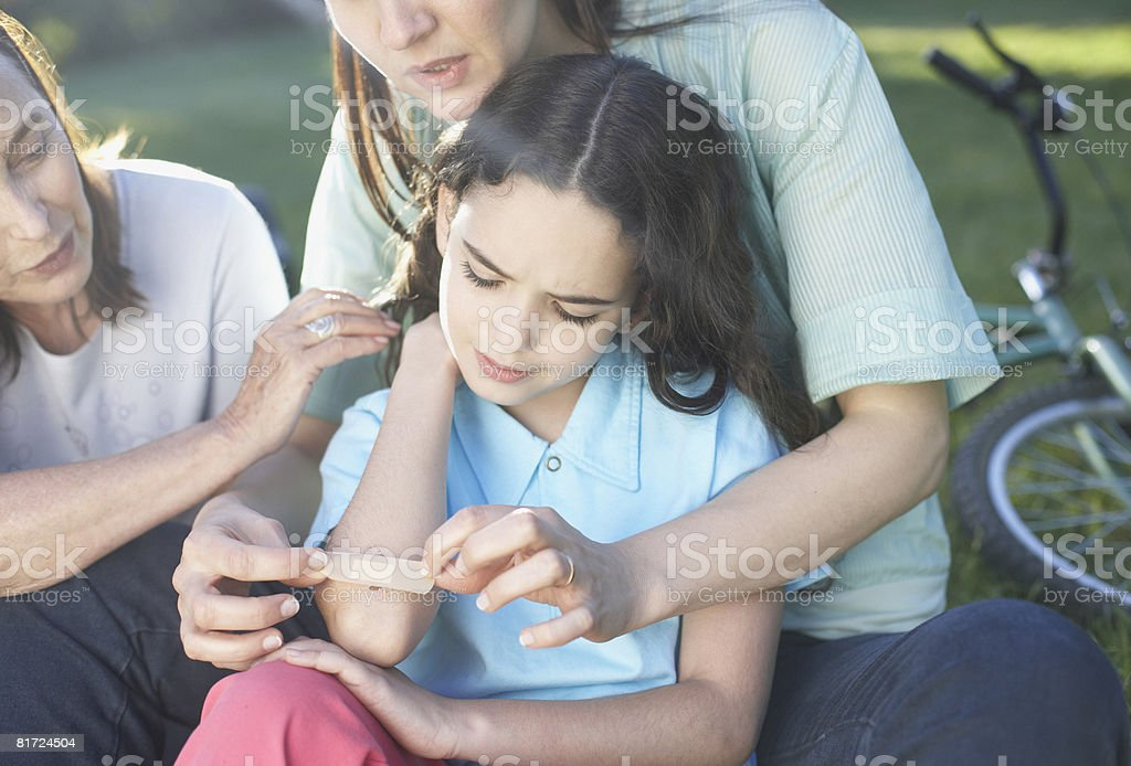 Two women helping an injured young girl who fell off her bike royalty-free stock photo