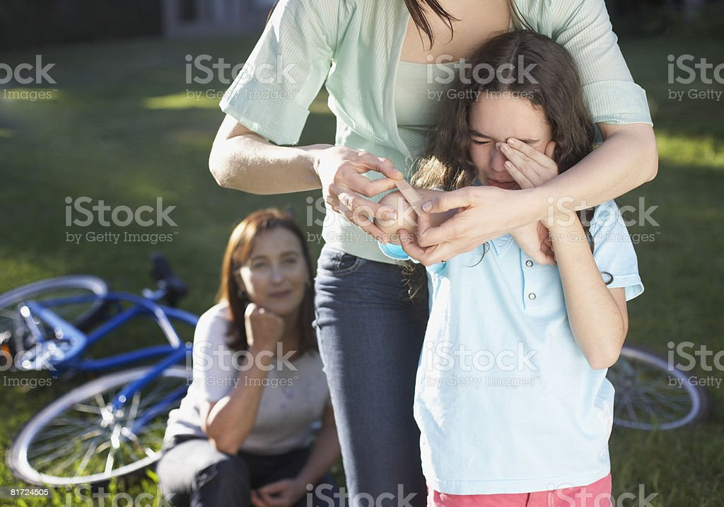 Two women helping an injured young girl who fell off her bike stock photo