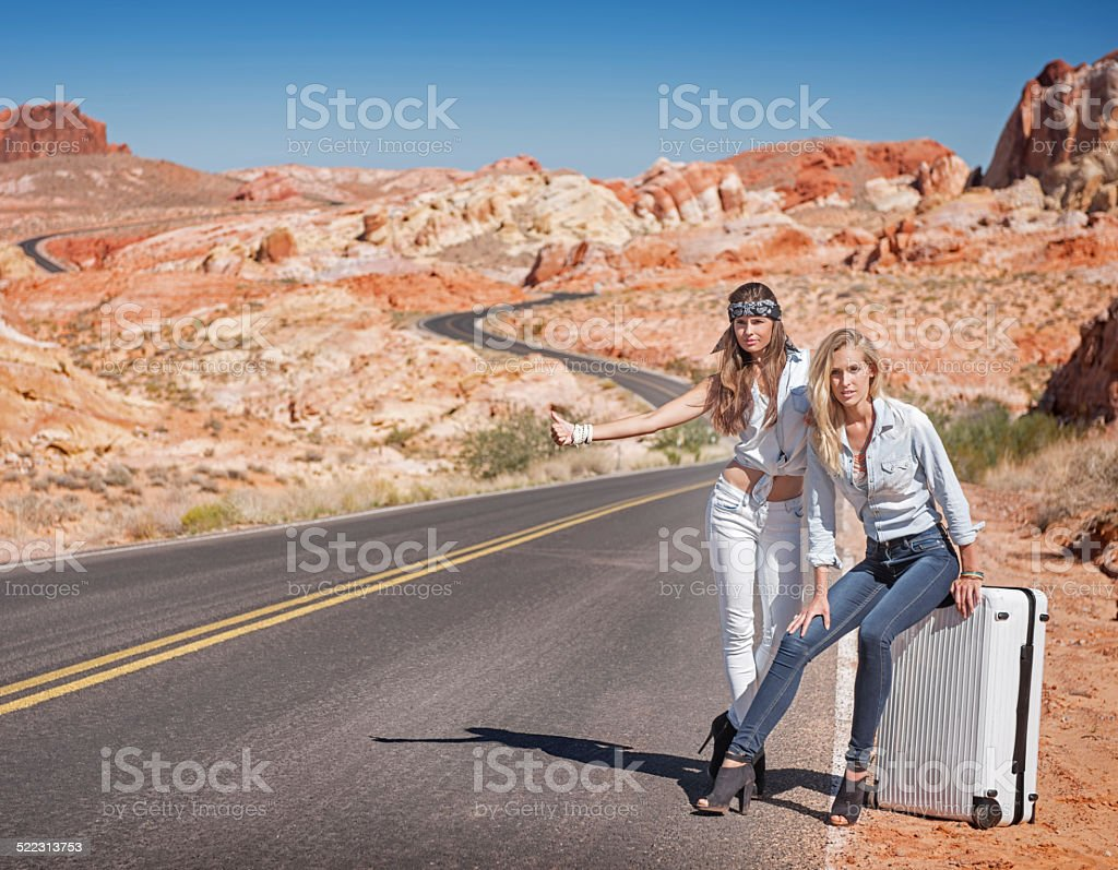 Two Women Hitchhiking in the Desert stock photo
