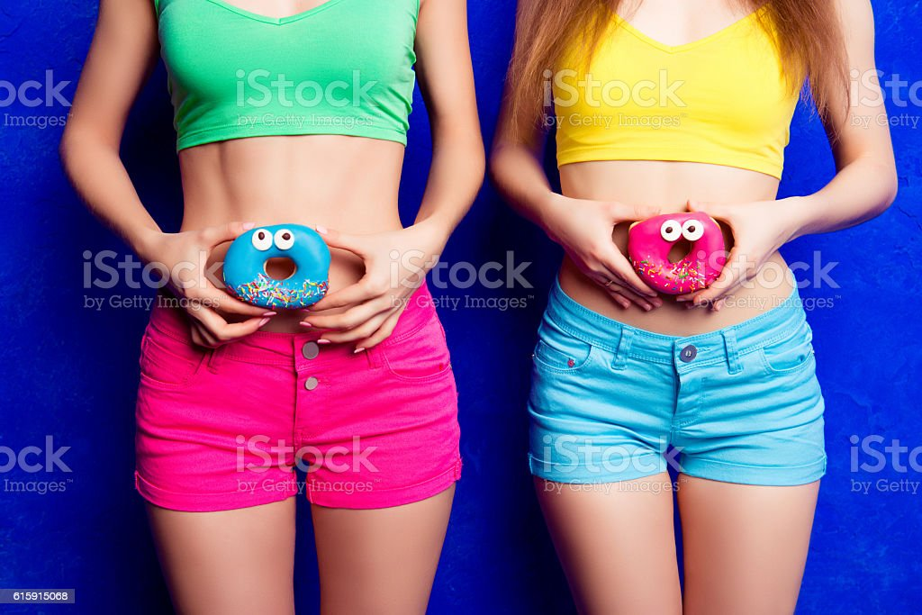 two women holding donutes near slim bellies stock photo