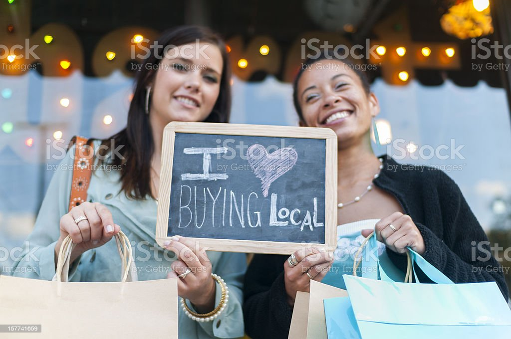 Two women holding up sign for buying local stock photo
