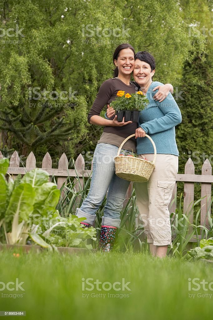 Two women hugging in garden stock photo