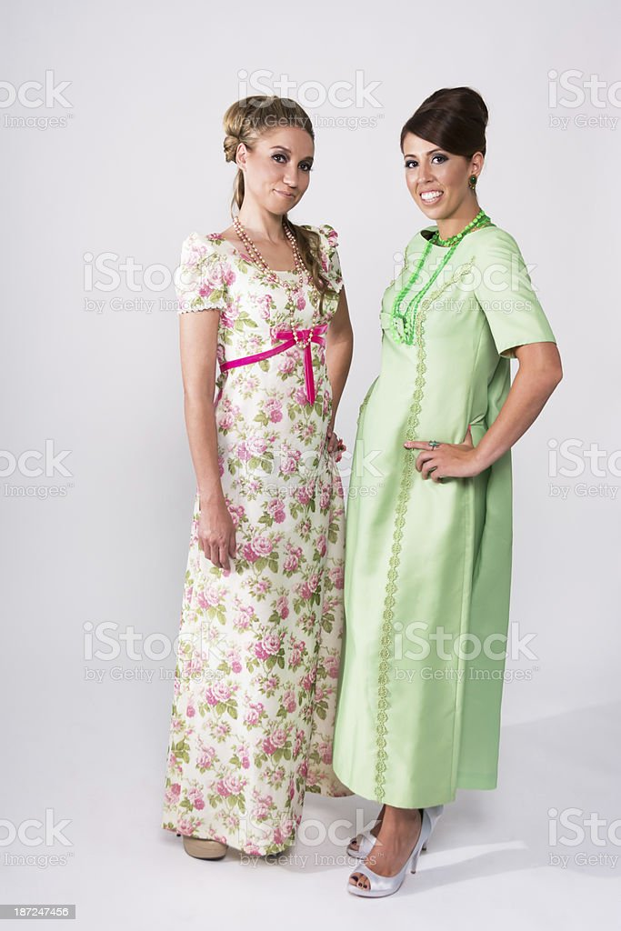 Two women in 60s style long dresses. stock photo