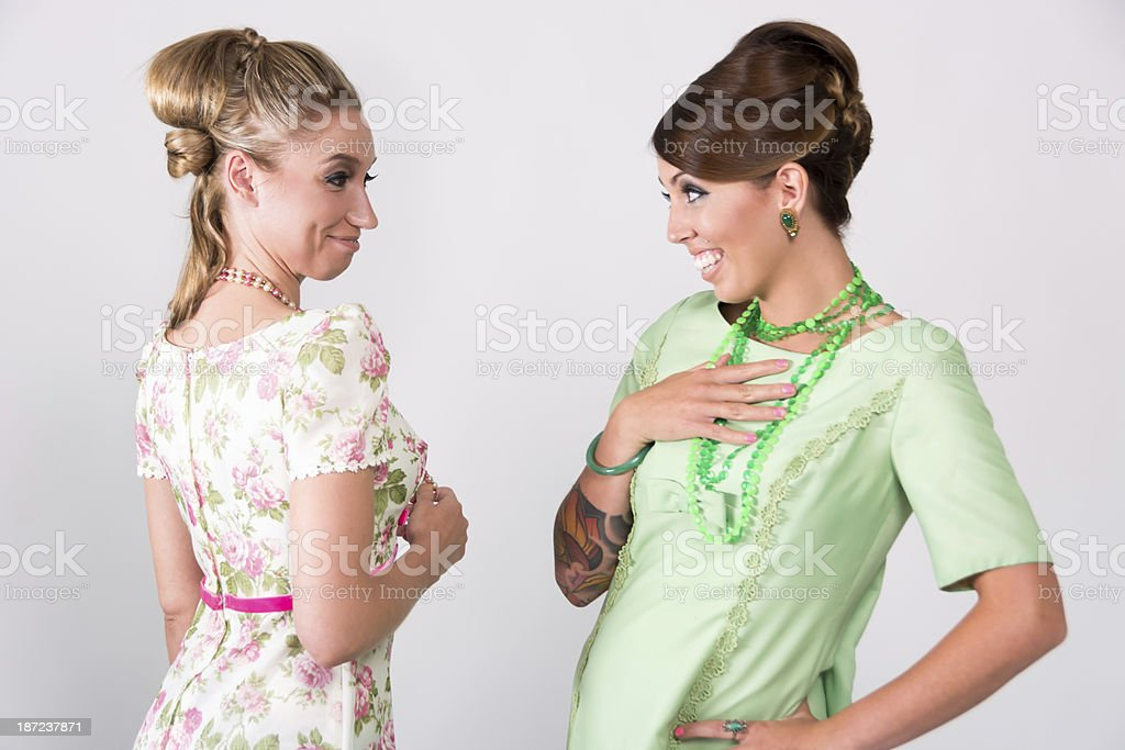 Two women in 60s styled hair etc gossiping. stock photo