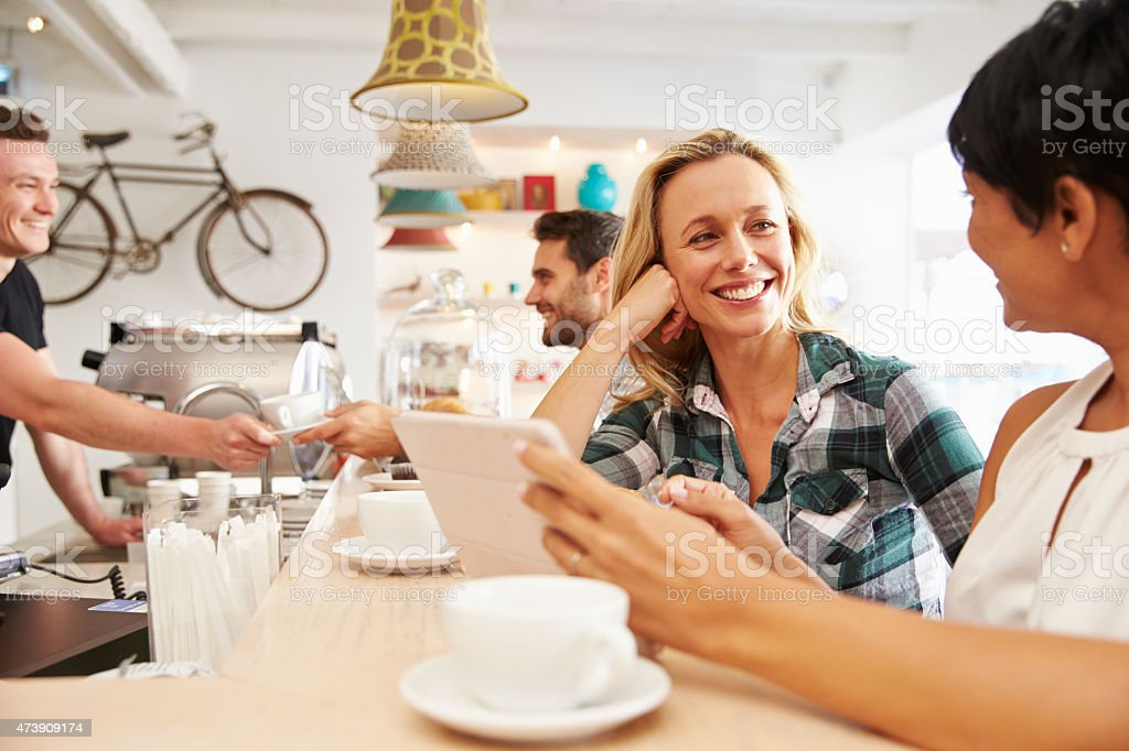 Two women in a cafe holding a digital tablet stock photo