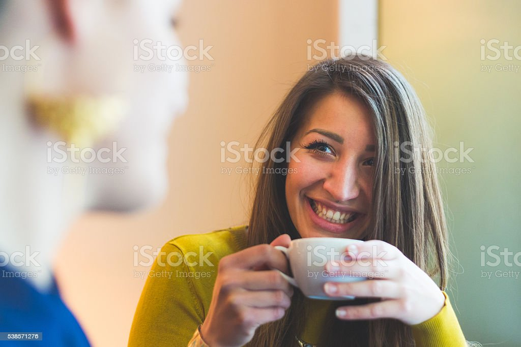Two women in a cafe smiling and looking each other stock photo