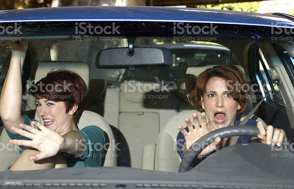 Two women in a car reacting to a crash stock photo