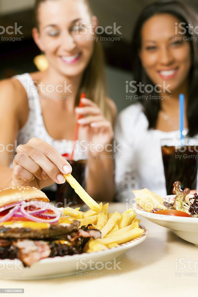 Two women in a restaurant eating hamburgers royalty-free stock photo