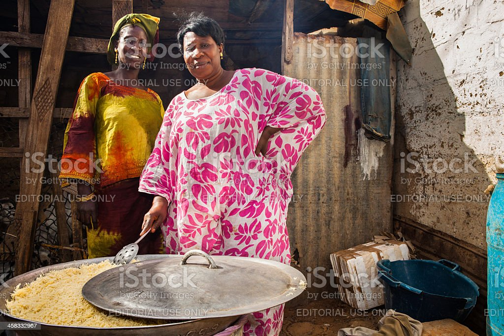 Two women in an african kitchen cooking for a party. stock photo