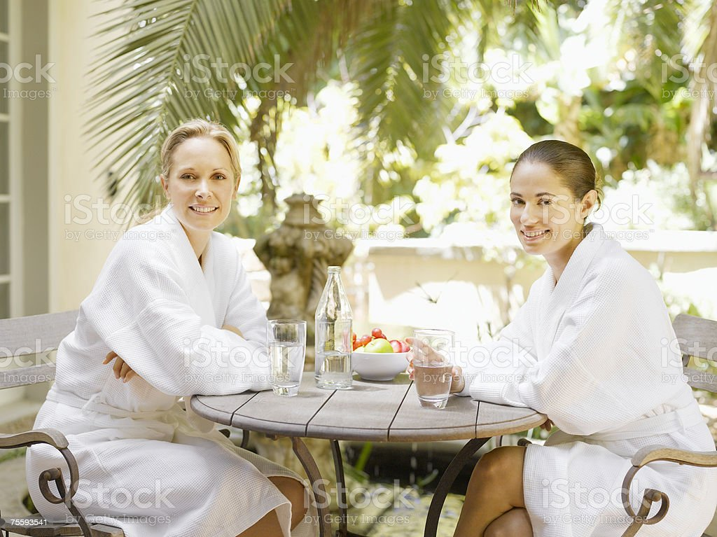 Two women in bathrobes sitting at a table outdoors royalty-free stock photo