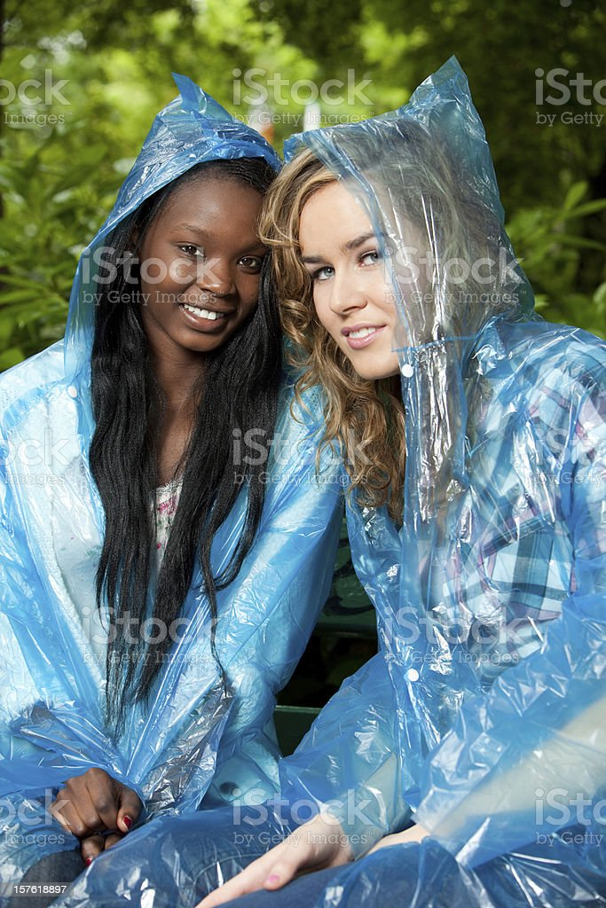 Two women in blue plastic rain poncho's stock photo