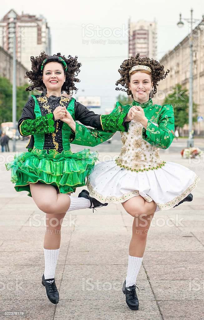 Two women in irish dance dresses and wig dancing stock photo