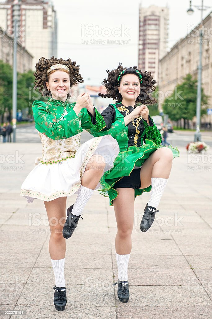 Two women in irish dance dresses and wig dancing stock photo