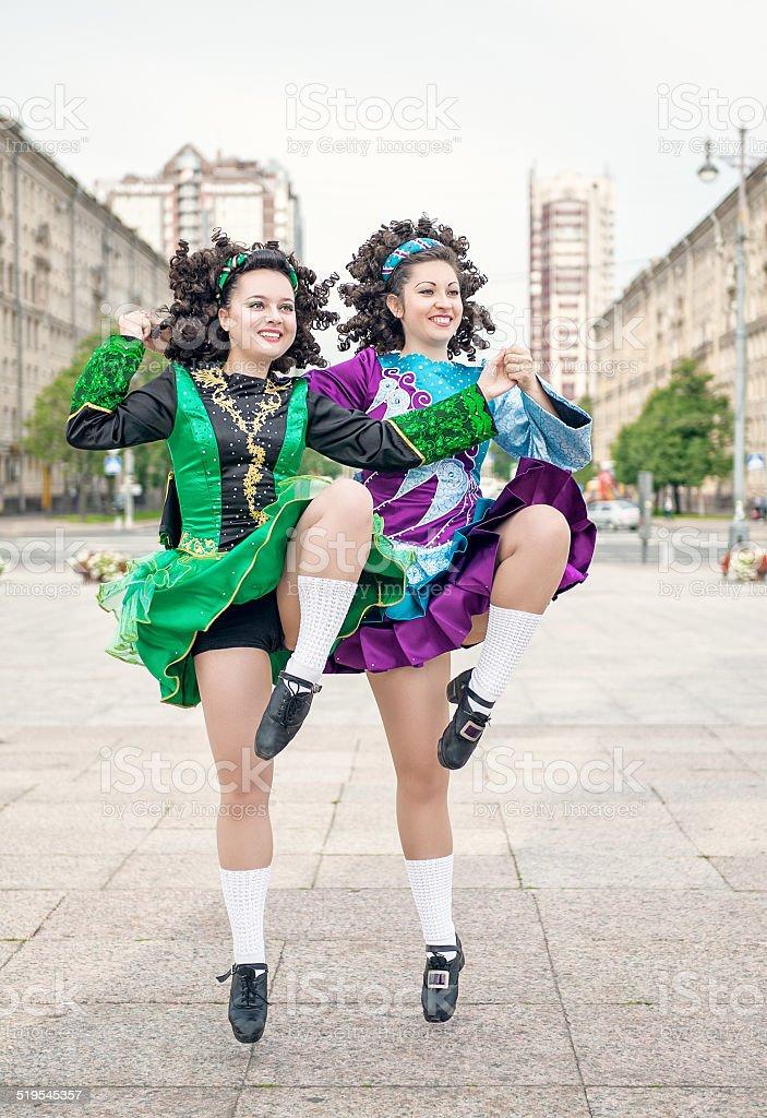 Two women in irish dance dresses dancing stock photo