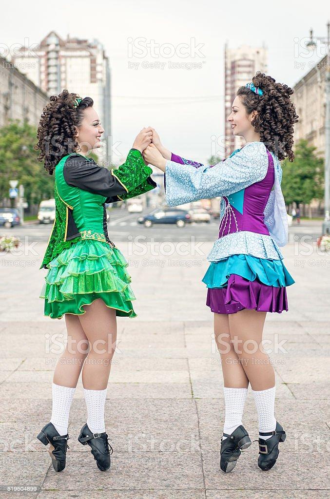 Two women in irish dance dresses posing stock photo