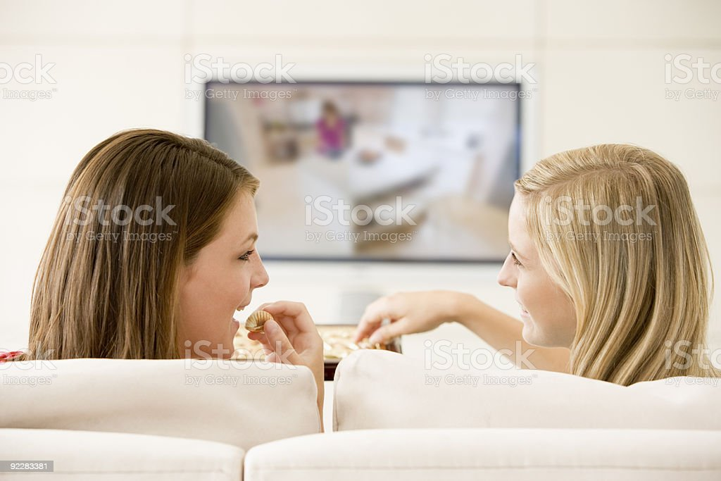 Two women in living room watching television eating chocolates stock photo