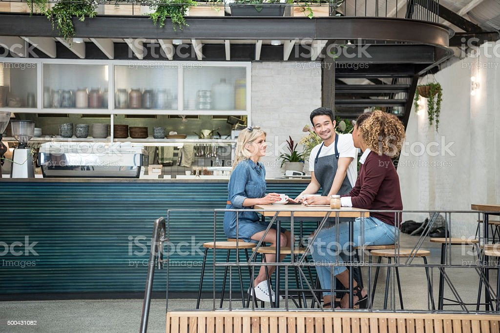 Two women in modern cafe with male waiter stock photo