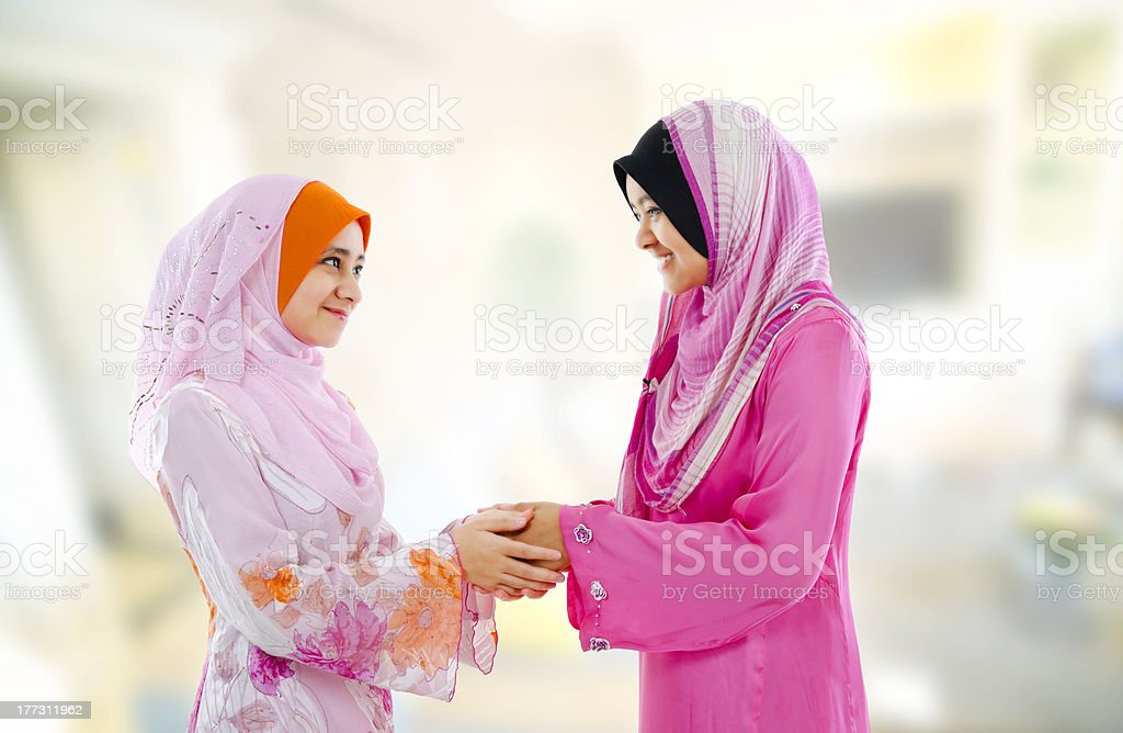 Two women in pink hijab smiling and holding hands stock photo