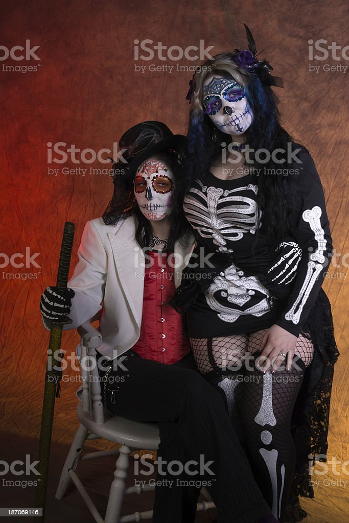 Two women in sugarskull makeup, sitting on one chair stock photo