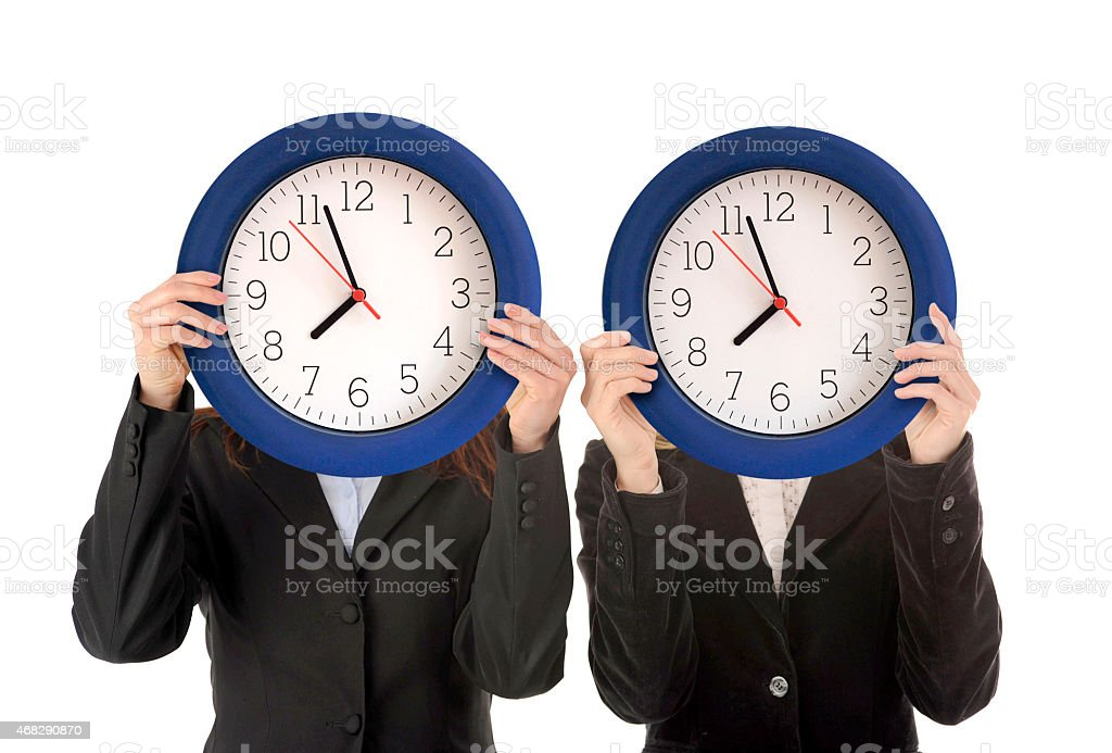 Two women in suits holding analogue clocks in front of faces stock photo