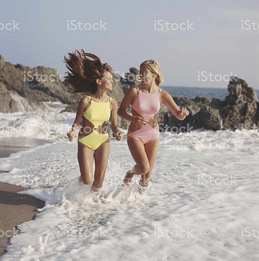 Two women in swimwear running on beach, smiling stock photo