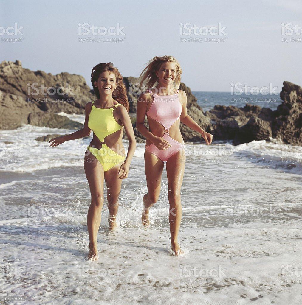 Two women in swimwear running on beach, smiling stock photo