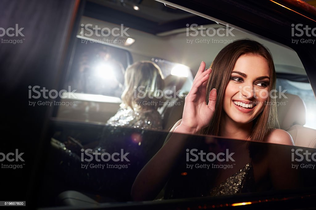 Two women in the back of a limo, photographed by paparazzi stock photo