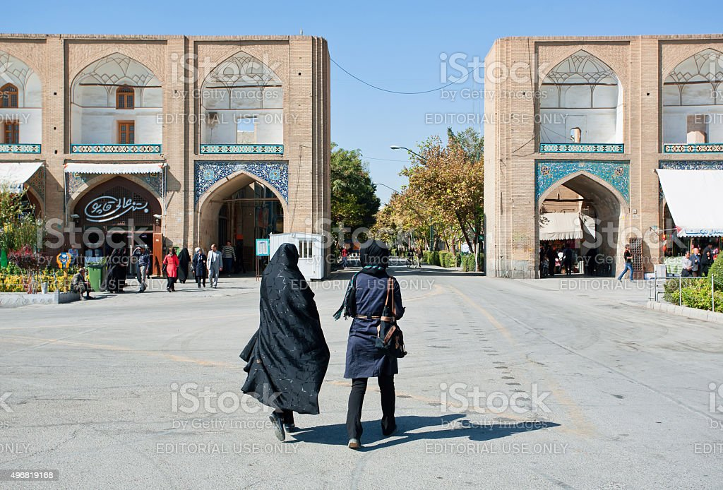 Two women in traditional hijabs rushing from Imam Square stock photo