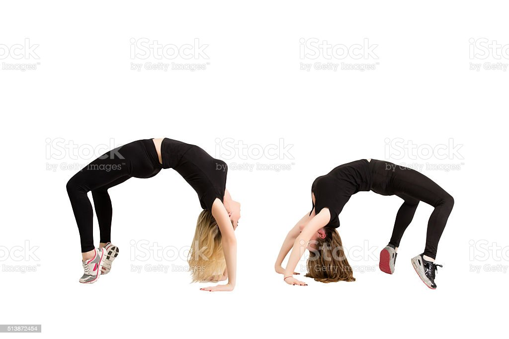 Two women in yoga pose bridge at fitness isolated stock photo
