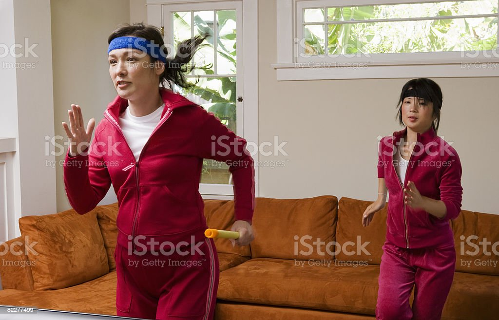Two women jogging in place in the living room stock photo