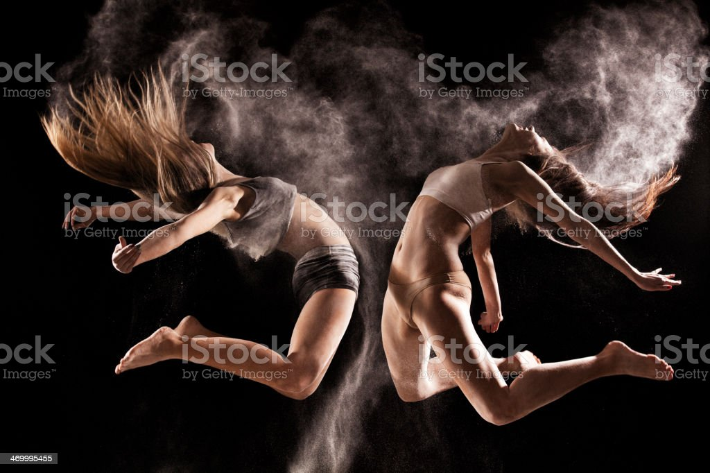 Two women jumping in a cloud of  powder stock photo