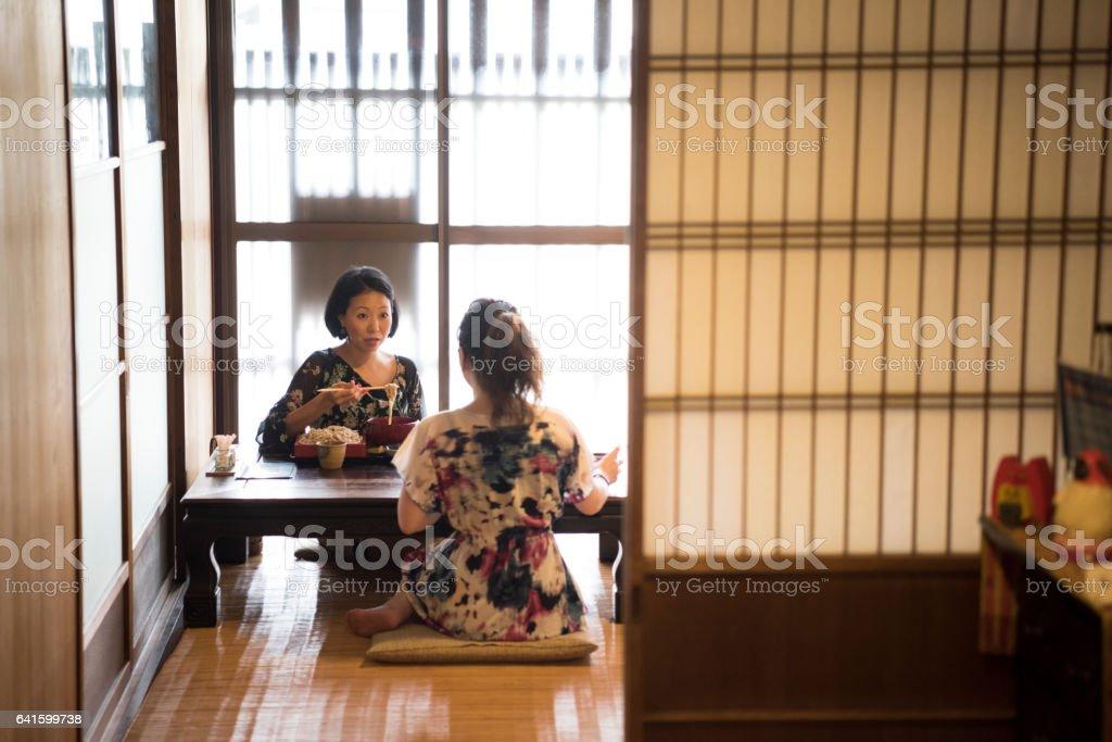 Two women kneeling on floor in traditional Japanese restaurant stock photo
