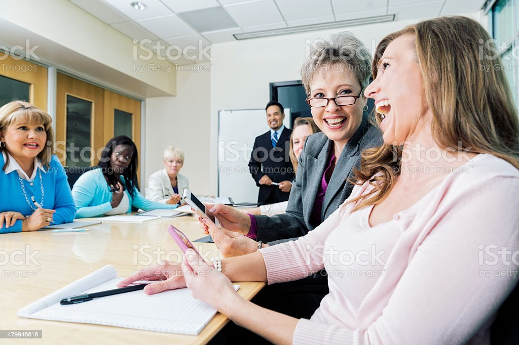 Two Women Laugh at Cell Phone Images at Business Meeting stock photo