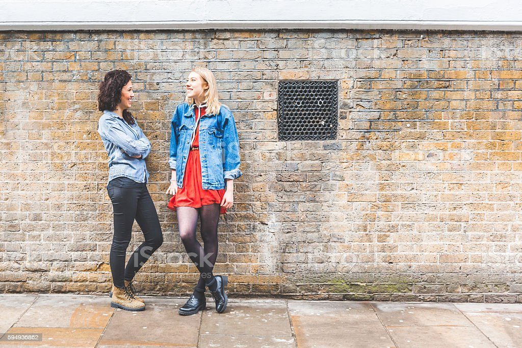 Two women leaning on a wall and talking in London stock photo