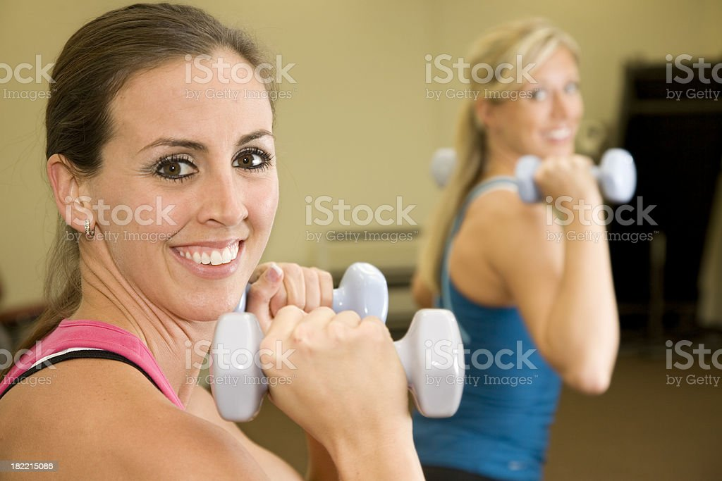 Two Women Lifting Bar Bells in a Fitness Class royalty-free stock photo
