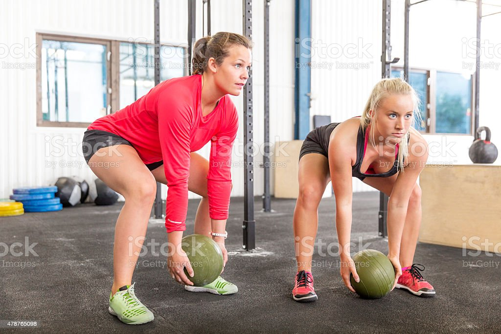 Two women lifts gym slam balls stock photo