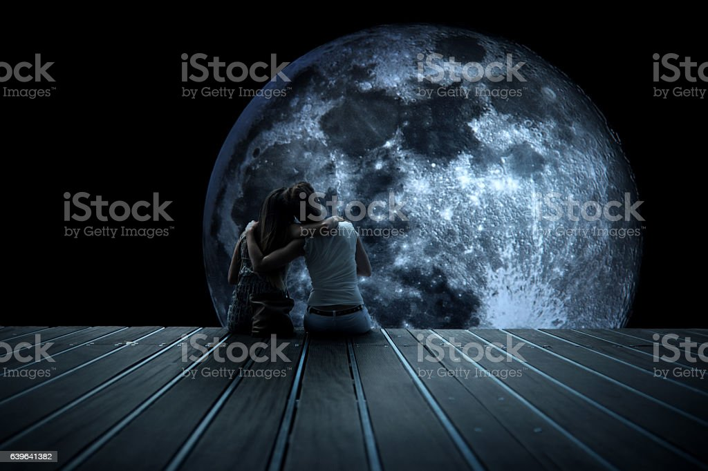 Two women look at the moon stock photo