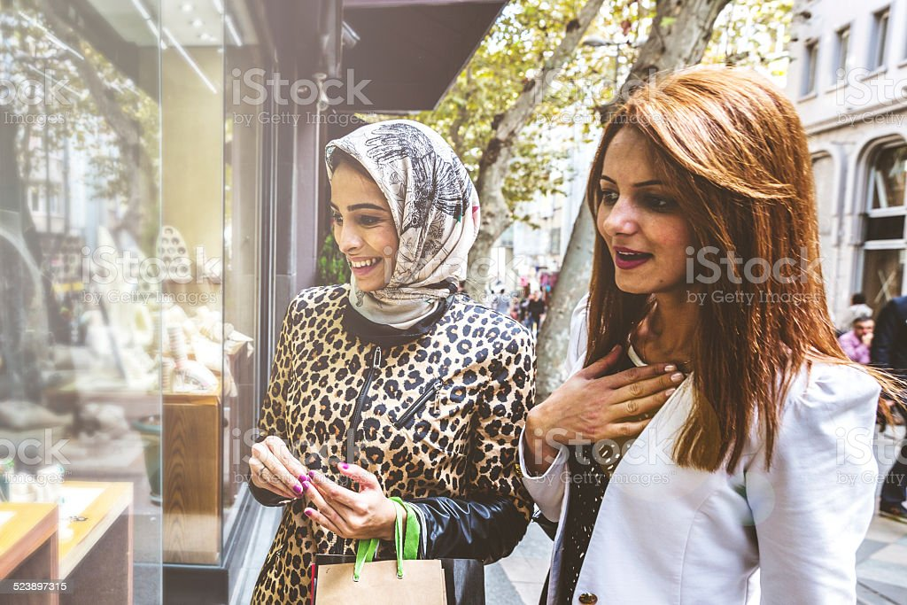 Two women looking at a jewelry store window. stock photo